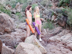 Redhead chick is stroking blonde girlfriend's cunt on rock